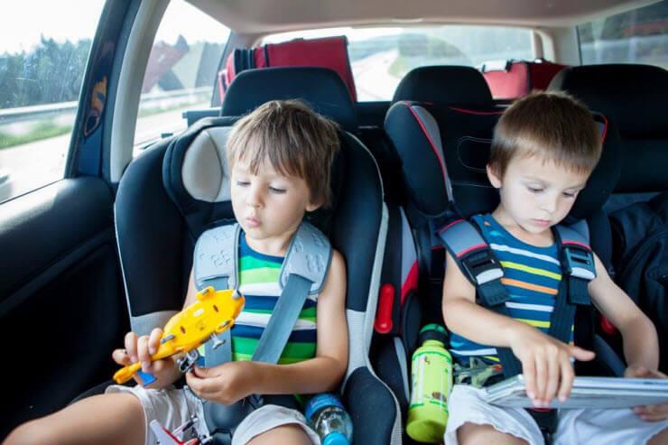 Cómo viajar con niños largos trayectos en coche - dos ninyos jugando en el coche