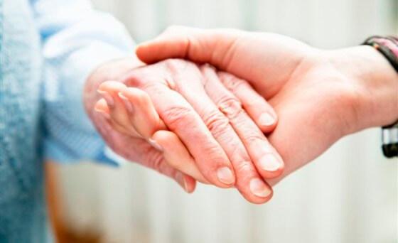 Cogiendo la mano de una persona mayor