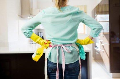 mujer de pie y de espaldas con la botella del aerosol y servilleta en la cocina