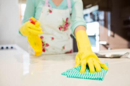 Mujer con guantes amarillas limpiando