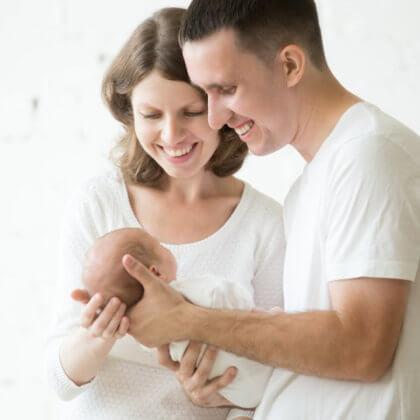 joven pareja mirando a su bebé recién nacido