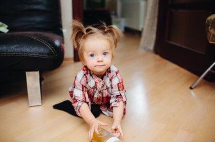 niña pequeña en el suelo cogiendo su biberón