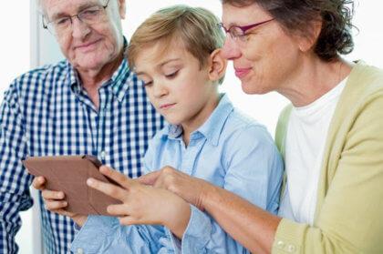 Domótica para personas mayores-Niño enseñando a mayores en tablet