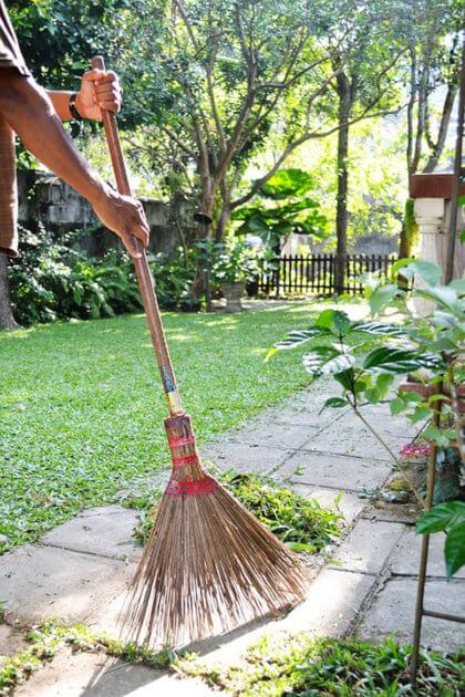 Cómo limpiar y mantener tu jardín en verano-recojiendo la hierba cortada