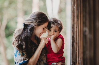 mujer con un niña en brazo jugando