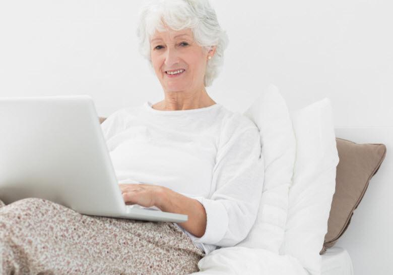 Bien cuidador de mayores-mujer mayor con portátil