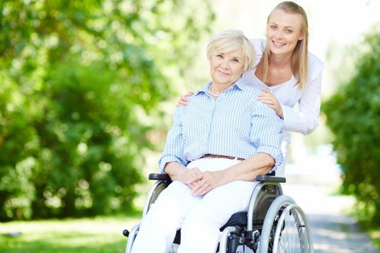Cuidador o cuidadora - cuidadora con persona mayor en silla de ruedas