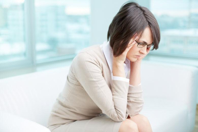 mujer preocupada sentada en sofa