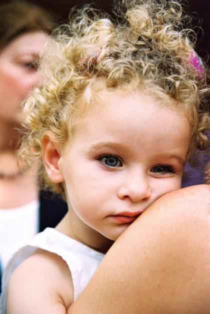 niña con rizos con mirada pensative en brazos de su madre