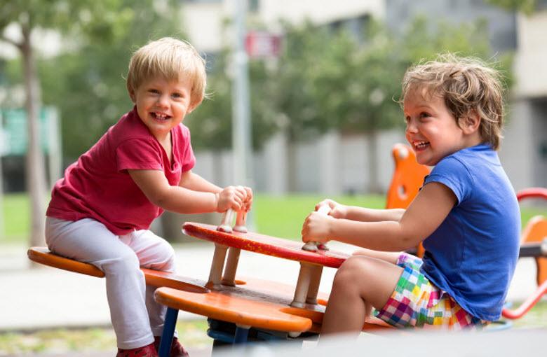 dos chicos en el columpio del parque infantil