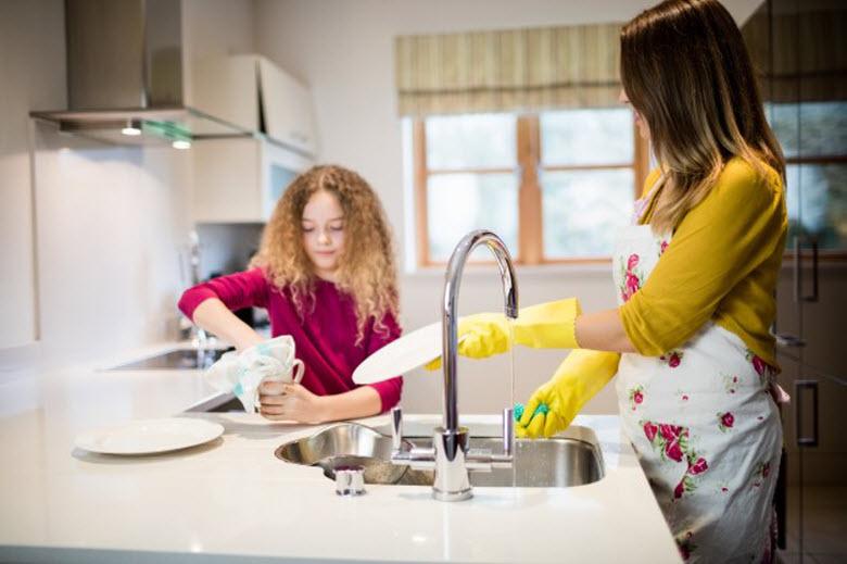 madre e hija limpiando y fregando los platos