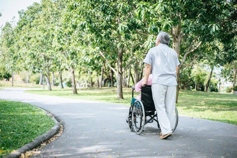 cuidador paseando persona mayor en silla de ruedas