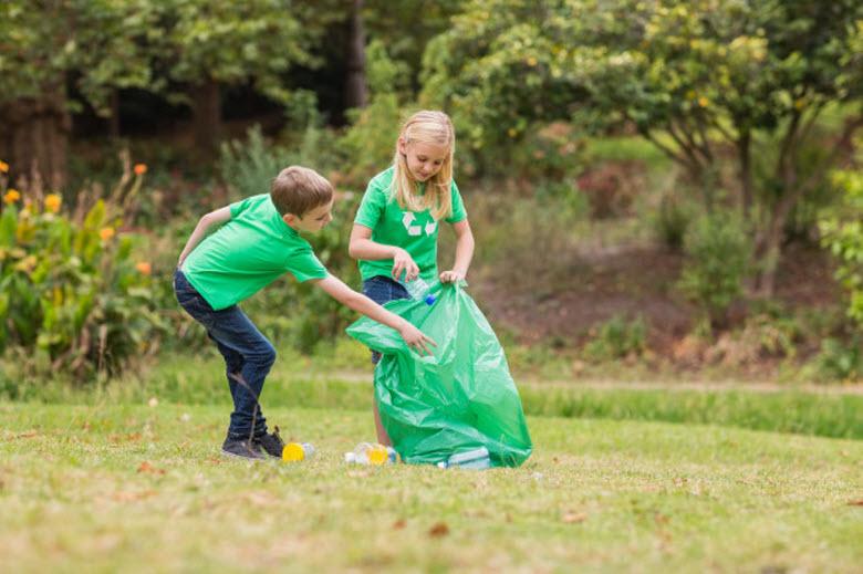 dos niños recogiendo basura en un parque para reciclar