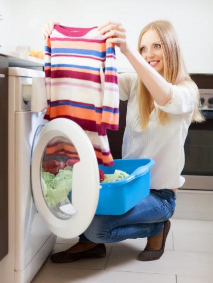 mujer sacando de la lavadora la ropa limpia
