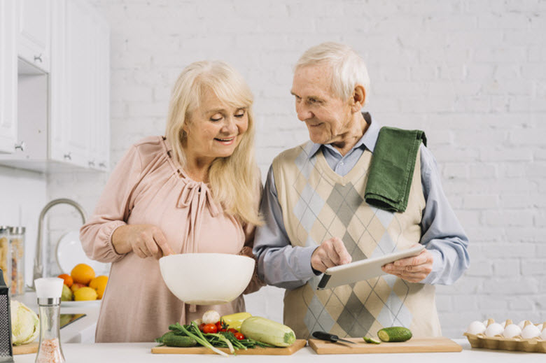 pareja de personas mayores cocinando juntos