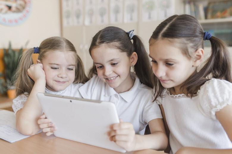 tres chicas mirando una tableta