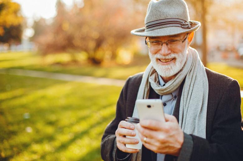 hombre mayor mirando su teléfono móvil