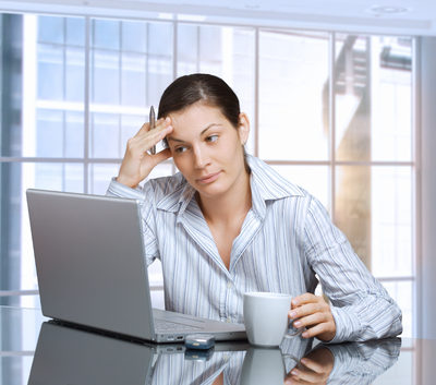 Mujer cansada delante de portátil