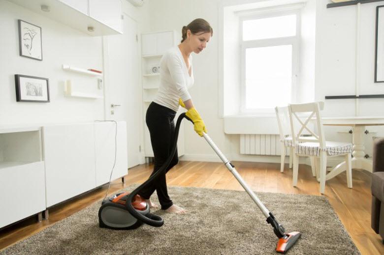 empleada de hogar aspirando la alfombra en el salón