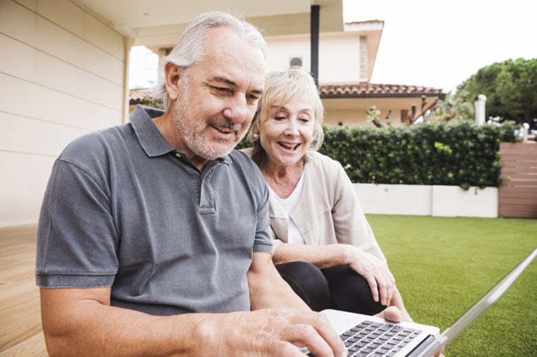 pareja de personas mayores mirando un PC portátil