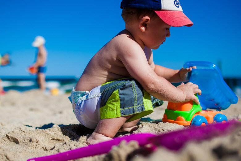 niño con gorra jugando en la arena