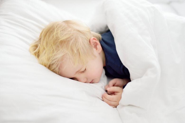 niño durmiendo de lado en cama blanca
